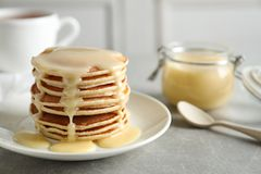 Plate with pancakes and condensed milk on table, space for text. Dairy product royalty free stock photos