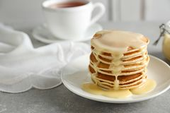 Plate with pancakes and condensed milk served on table, space for text royalty free stock photo