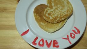 A plate with pancakes in the form of a heart and a mug with coffee on a table. Pancakes in the form of heart lie on a plate on the edge of which words are stock footage