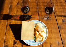 Plate with parmigiana regiano cheese and red wine royalty free stock image