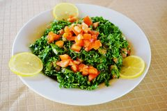 Plate of parsley and tomato tabbouleh with lemon wedges. Plate of parsley and tomato tabbouleh (tabouli), a traditional Middle Eastern salad, with lemon wedges Royalty Free Stock Image