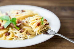 Plate of Pasta Carbonara and Spaghetti with bacon and parmesan cheese on a fork on old wooden table Stock Photos