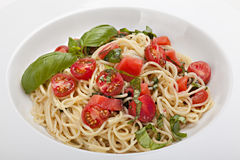 Plate of pasta with fresh tomatoes and basil . Royalty Free Stock Images