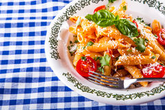 Plate with pasta pene Bolognese sauce cherry tomatoes parsley top and basil leaves on checkered blue tablecloth. Stock Photos
