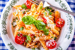Plate with pasta pene Bolognese sauce cherry tomatoes parsley top and basil leaves on checkered blue tablecloth. Italian and Mediterranean cuisine Stock Images