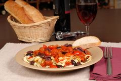 A plate of pasta puttanesca with wine and bread. Plate of pasta puttanesca with wine and bread stock image