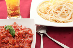 Plate of pasta with tomato. Pasta dish with minced meat with tomatoes and beer with knife and fork Stock Photo
