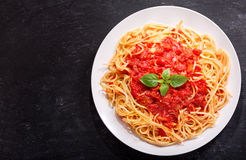 Plate of pasta with tomato sauce and green basil Stock Images