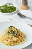 A plate of pasta with zucchini. And some rocket salad in the background royalty free stock photo