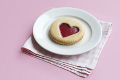 Plate with pastry on pink background. Pastry with jam heart on a plate on pink background Stock Image