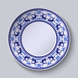 Plate with pattern in gzhel style of painting on porcelain. Wide ornament along the edge with flowers and birds. Stock Photos