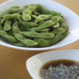 Plate of pea pods. And bowl of sauce on table stock image