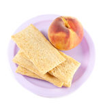 A plate with peach and three crisps Royalty Free Stock Photography