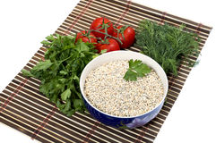 Plate with pearl barley, nearby parsley, tomatoes, fennel Royalty Free Stock Photos