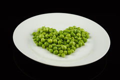 Plate with peas shaped as a heart. White plate with green peas shaped as a heart Royalty Free Stock Photos