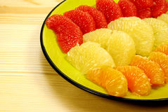 Plate with peeled citrus segments. Peeled citrus segments on a green plate, peeled grapefruits and mandarine; the plate is on a wooden table Royalty Free Stock Photography