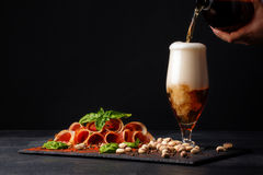 A plate of perfectly sliced balyk and a man's hand add beer in a glass on a dark background. Cured prosciutto with a basil and a stock images