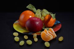 Plate with persimmon apple grapes and tangerine on a black background, close-up stock photography