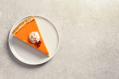 Plate with piece of fresh delicious homemade pumpkin pie on gray background, top view stock image