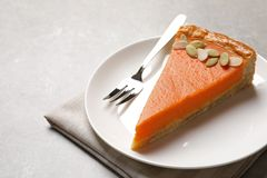 Plate with piece of fresh delicious homemade pumpkin pie on light table royalty free stock image