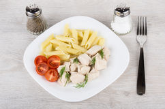 Plate with pieces chicken, pasta and tomatoes, fork Stock Image
