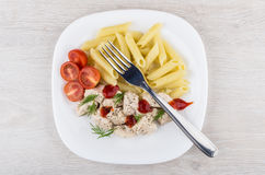 Plate of pieces chicken, pasta and tomatoes on table Royalty Free Stock Image