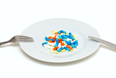 Plate with pills. Plate with colorful pills, knife and fork Royalty Free Stock Images