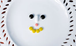 Plate with pills. Set in shape of face Stock Photo