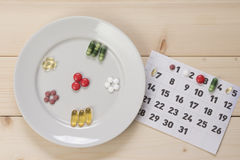Plate with pills and a calendar Stock Photography