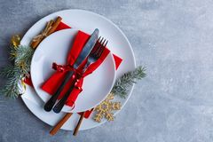A plate in a plate with a knife and fork lies facing in a side against a stone background. View from above Stock Photos