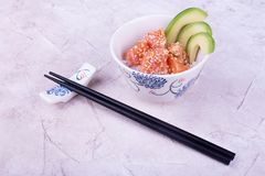 Plate with poke and sticks. Plate poke on beige table. Marine dish of fishermen Royalty Free Stock Image