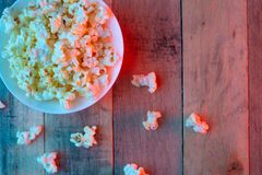 Plate with popcorn on a wooden background, concept of cinema, cinema and entertainment, creative light, blue and red, layout, stock photo