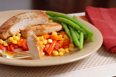 Plate of pork chops resting on a bed of corn, peppers and onions Royalty Free Stock Photography