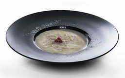 Plate of porridge on white table. Cooked porridge with red berries in black mat plate on white surface stock photo
