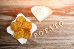 Plate with potato pancakes and sour cream. Inscription Potato. Gray wooden background, top view Stock Image