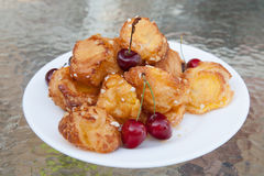 The plate of profiteroles on glass table Royalty Free Stock Image