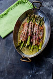 A plate of prosciutto wrapped asparagus. Delicious baked prosciutto wrapped asparagus Stock Photos
