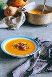 A plate of pumpkin soup with a jamon, garlic, thyme and cream royalty free stock images
