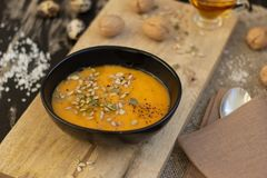 Plate of pumpkin soup on wooden cutting board royalty free stock image