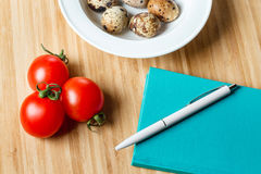 Plate with quail egg, tomatoes cherry and diary with pen on wooden table. Top view. For Recipe Stock Photos