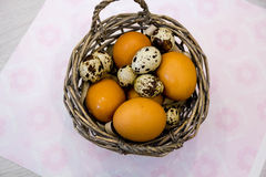 Plate with quail eggs and chicken eggs. Quail eggs in a wooden bowl. place for text. nutrition protein diet. Top view, flat lay wi Stock Photos