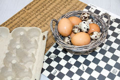 Plate with quail eggs and chicken eggs. Quail eggs in a wooden bowl. place for text. nutrition protein diet. Top view, flat lay wi Royalty Free Stock Images