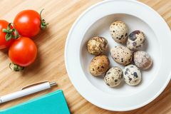 Plate with quail eggs, tomatoes cherry and diary with pen on wooden table. Top view. Concept Recipe. Stock Image