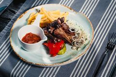 Plate with rack of lamb, grilled vegetables, bow, sauce and french fries. Clouse up. On the background of a table with a royalty free stock photography