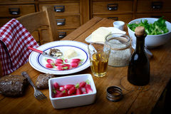Plate with radish, butter and salad on a table. Plate with radish, butter and salad on old table Royalty Free Stock Images
