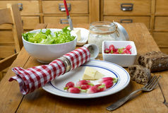 Plate with radish and butter on a table. Plate with radish, butter and salad on a table Stock Photography