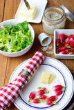 Plate with radish and butter on a table. Plate with radish, butter and salad on a table Royalty Free Stock Photo