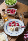 Plate with radish and butter on a table. Plate with radish, butter and salad on a table Royalty Free Stock Photography