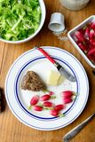 Plate with radish and butter on a table. Plate with radish, butter and salad on a table Stock Image