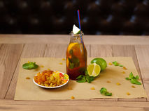 A plate with raisins and dried apricots, a cocktail with lemon, a cocktail, juicy slices of lime on a blurred light Royalty Free Stock Photography